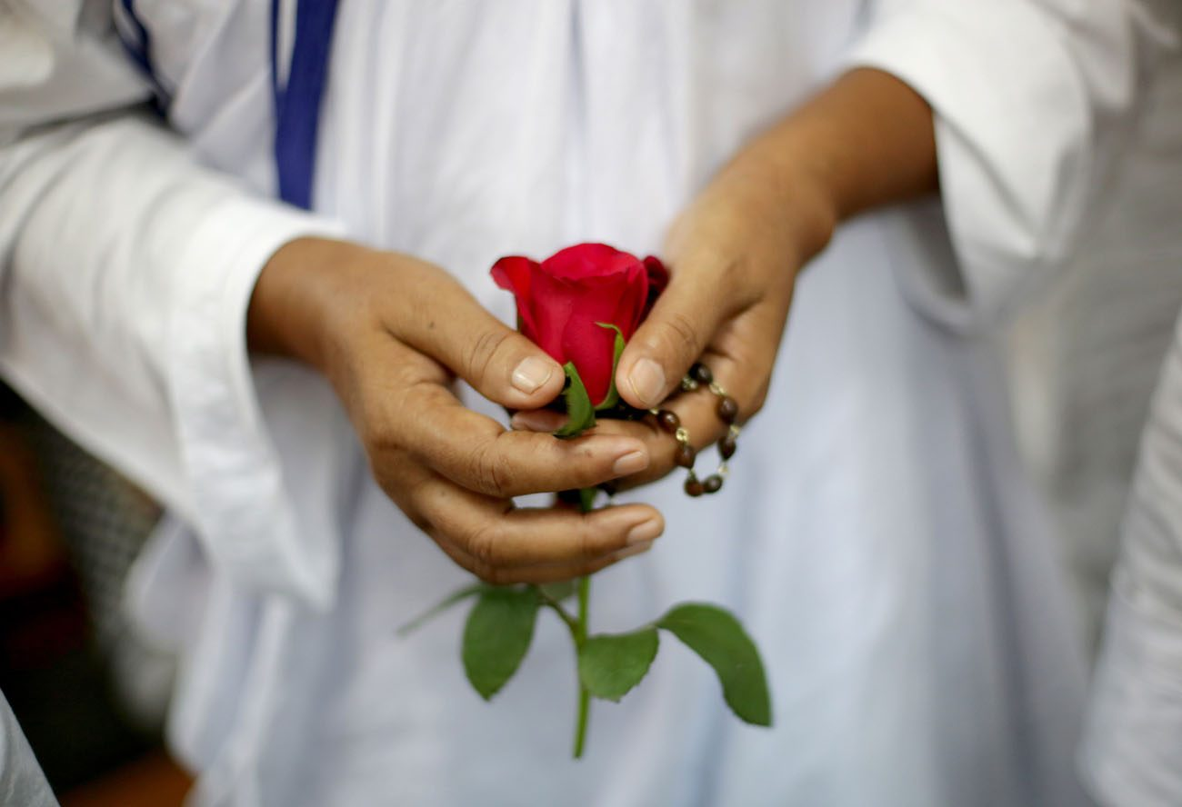 "A Missionaries of Charity nun holds a rose in Kolkata, India, Sept. 5. Pope Francis said during Sept. 8 Mass in the chapel of the Domus Sanctae Marthae that men and women are called to build peace every day ""in the little things"" in life. (CNS photo/Piyal Adhikary, EPA)"