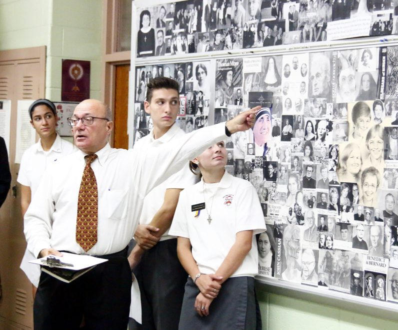 Retired Archbishop Ryan High School teacher Ed Lawrence shows some of the saints on a collage in his former classroom that inspired his efforts to create the new prayer initiative. (Sarah Webb)