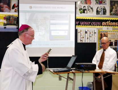 Bishop Michael Fitzgerald blesses the computer displaying the website Prayers Unite the World during a program Sept. 19 at Archbishop Ryan High School. (Sarah Webb)