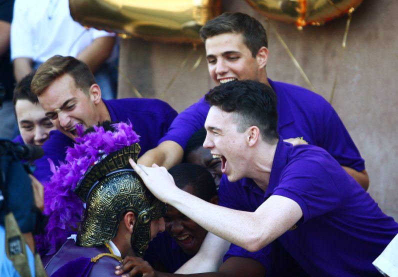 Patrick Doyle (right), student council vice-president, celebrates with fellow Roman Catholic students as their mascot won the race earning them a dress-down day.
