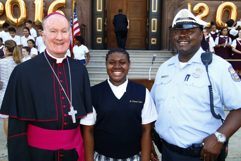 Bishop Fitzgerald poses for a photo with Philadelphia Police Officer Steven Leach and his daughter Gabrielle, who is an eighth grade student at St. Francis Xavier School in nearby Fairmount. Officer Leach was assigned to help with the closure of 18th Street during during the pep rally.