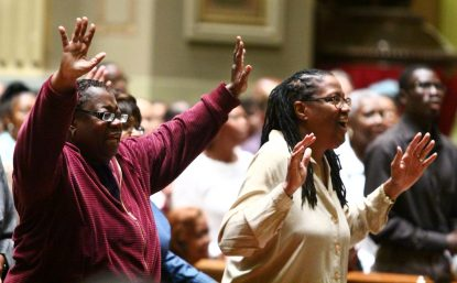 From left, Ora King of St. Vincent de Paul Parish and Alice Yellock of St. John the Evangelist Parish praise the Lord at the revival.