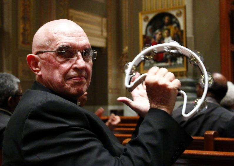 Vincentian Father Sy Peterka, pastor of St. Vincent de Paul Parish in the Germantown section of Philadelphia, sings along and plays his tambourine.