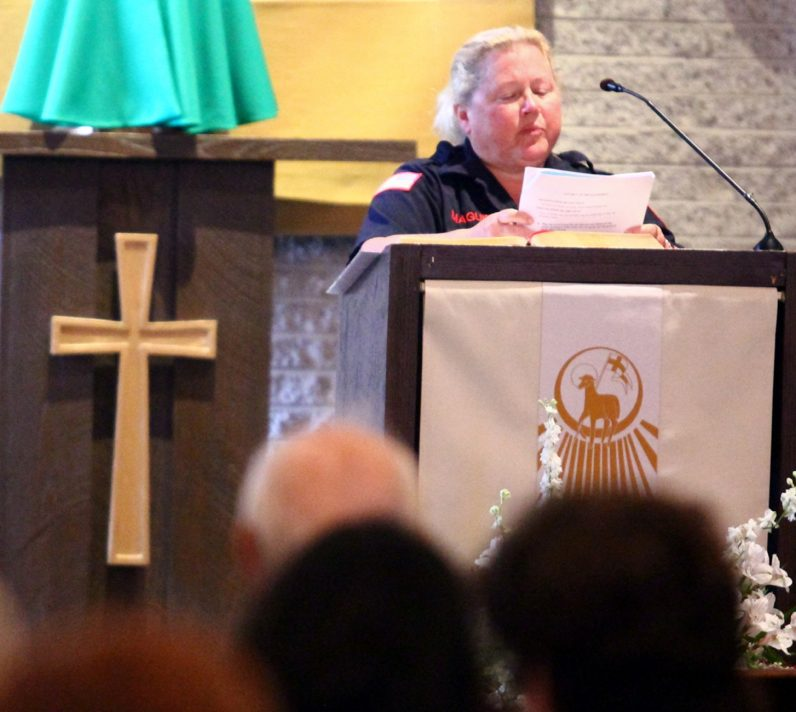 Virginia Maguire, an EMT with the Radnor Fire Company, proclaims a reading from Scripture at the Mass.