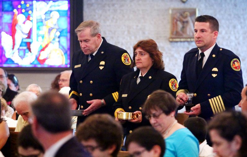 Local first responders bring up the offertory gifts during the Blue Mass at St. Isaac Jogues Church.
