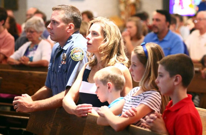 Officer Joseph Butler, director of the Community Policing Unit of the Tredyffrin Police Department and a member of St. Elizabeth Parish in Upper Uwchlan, prays with his family during the Blue Mass at St. Isaac Jogues Church.