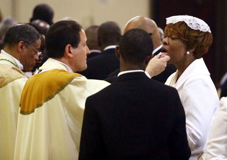 Bishop John McIntyre distributes holy Communion.