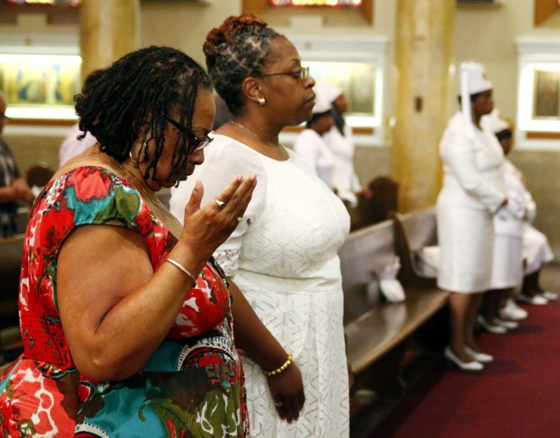 Dr. Renee Robinson (left) and her daughter Van pray together during the Mass for St. Peter Claver at St. Cyprian Church.