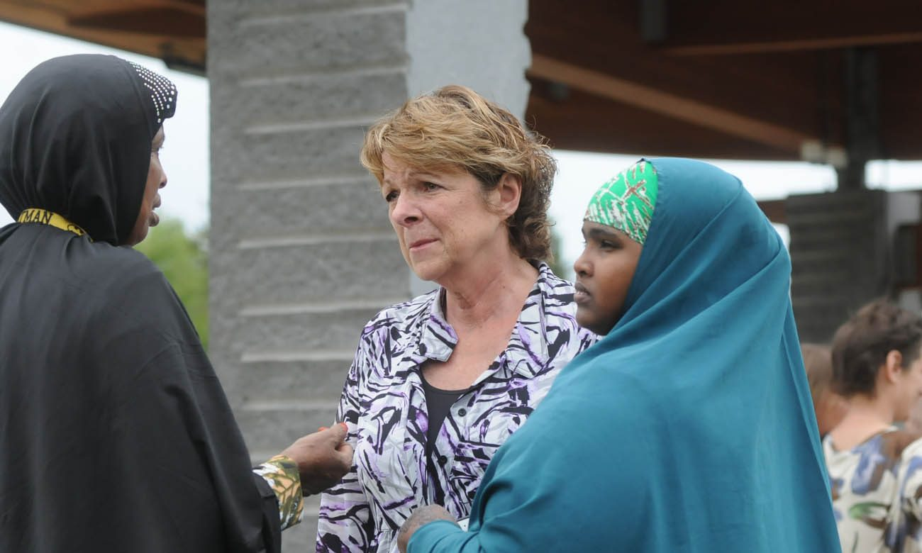Kathy Langer, director of social concerns for Catholic Charities of the Diocese of St. Cloud, Minn., center, talks with Maryan Ahmed and Fatumo Ukash following a Sept. 18 news conference organized by the local Somali-American community in St. Cloud after a knife-wielding man injured nine people the previous day at a shopping mall. (CNS photo/Dianne Towalski, The Visitor)