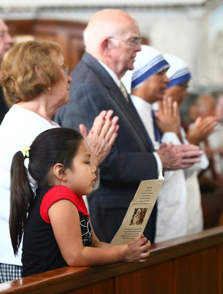 Victoria Castro prays along during a Mass honoring the canonization of St. Teresa.