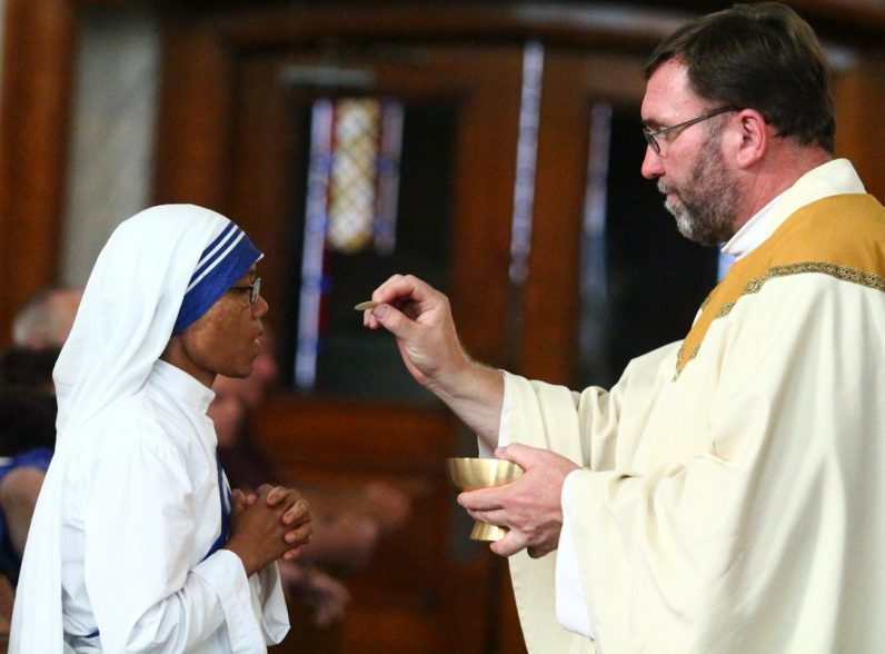 Father Christopher Walsh distributes holy Communion to a Missionary of Charity sister.