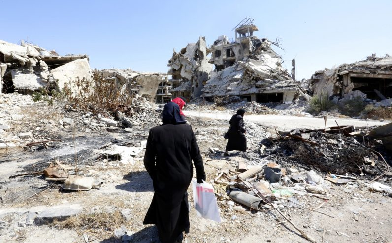 People walk amid rubble Sept. 19 in the city of Homs, Syria. (CNS photo/Mohammed Badra, EPA)