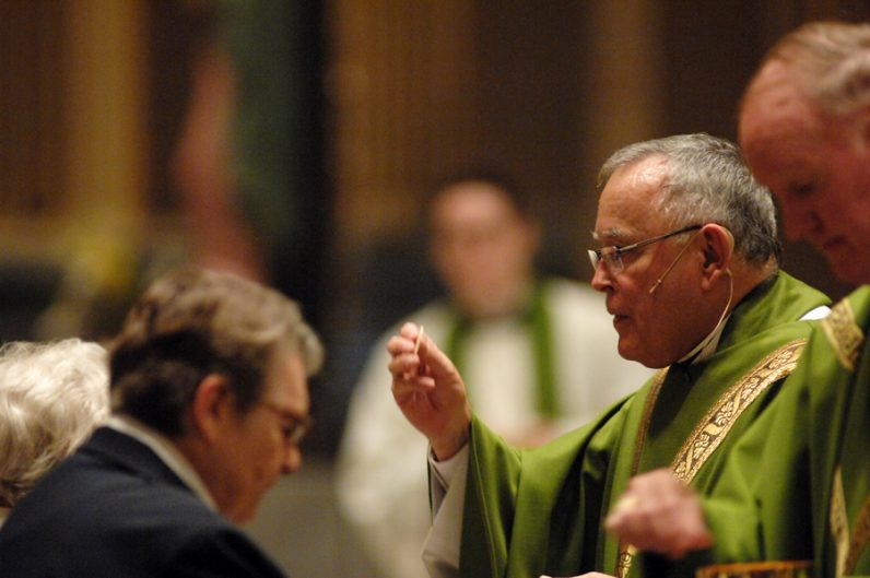Archbishop Charles Chaput, who celebrated the jubilarians' Mass Sept. 12 at the Cathedral Basilica of SS. Peter and Paul, distributes holy Communion to the religious sisters and other Catholics attending the Mass. (D'Mont Reese)