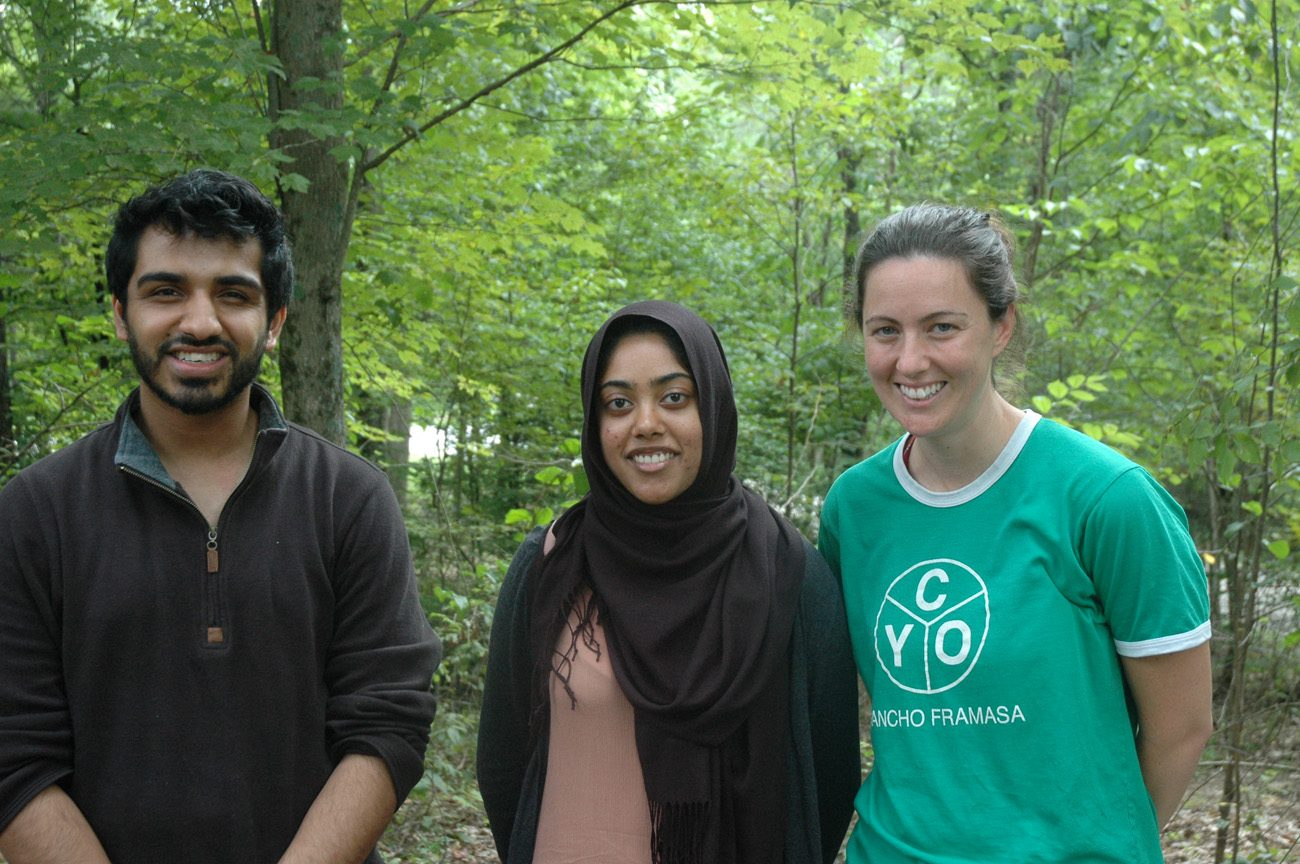 From left, Muslims Uzair Siddiqui, 23, and Fariha Hossain, 21, pose for a photo at Camp Rancho Framasa in Nashville, Ind., with Anne Taube, 30, a Catholic who is the camp's assistant director. In early August the camp was the setting for about 150 Muslim youths from across the country to enjoy a week of swimming, canoeing, climbing and learning about their faith as well as the Catholic faith. (CNS photo/John Shaughnessy, The Criterion)