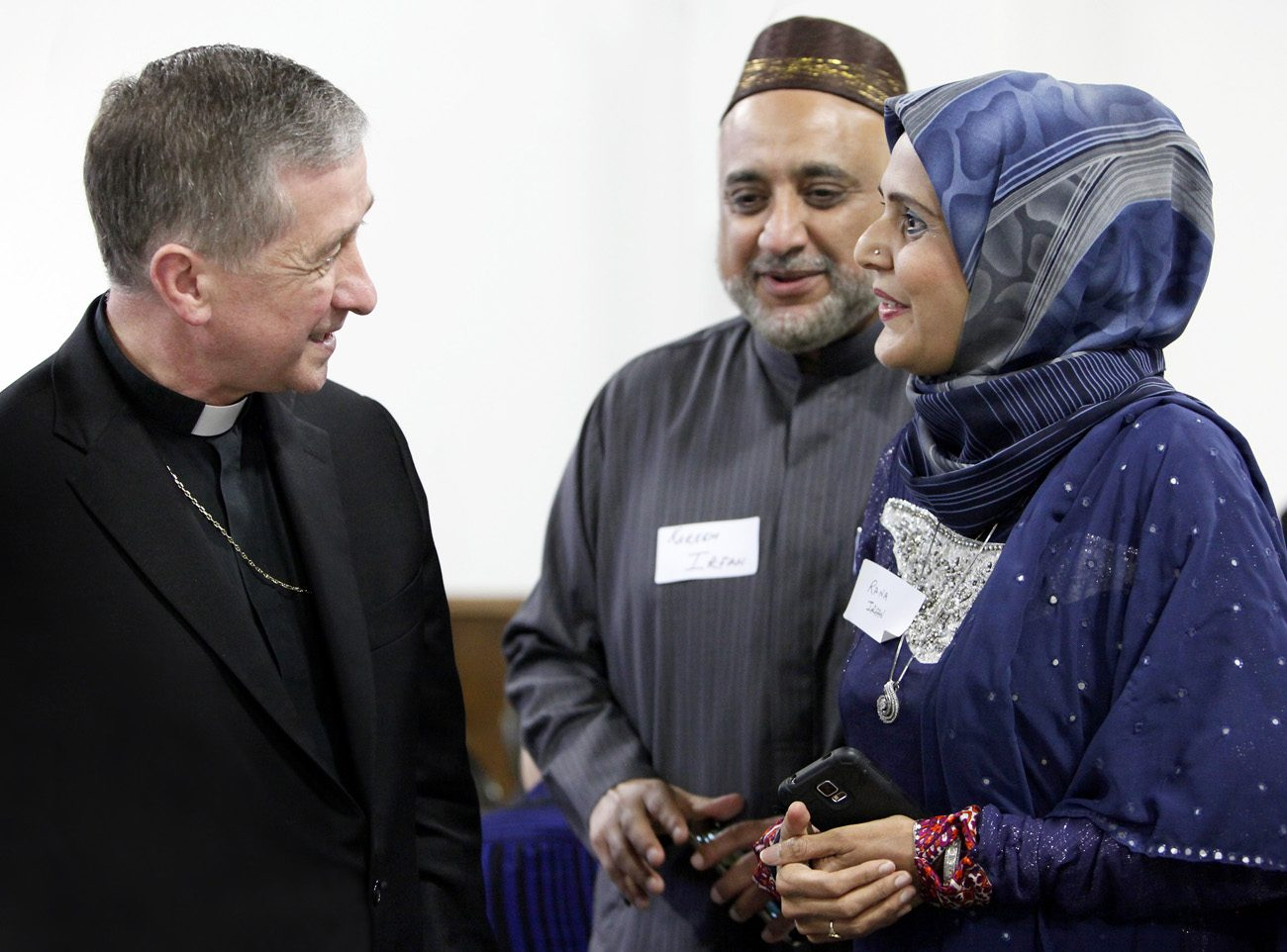 Chicago Archbishop Blase J. Cupich visits with a couple during a June 27 Catholic-Muslim dinner in Bridgeview, Ill. A Georgetown University research group found Catholic perceptions of Islam can tend to be negative or limited. (CNS photo/Karen Callaway/Catholic New World)