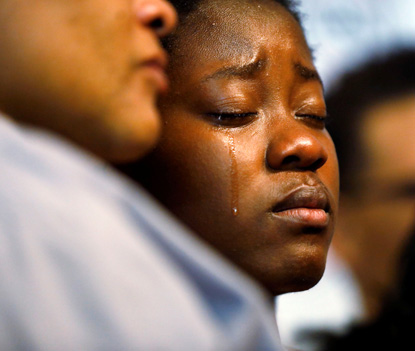 Tears stream down the cheeks of the daughter of Alfred Olango at a Sept. 28 a news conference held by Olango's family a day after the unarmed black man was shot dead by police in El Cajon, Calif. (CNS photo/Patrick T. Fallon, Reuters)