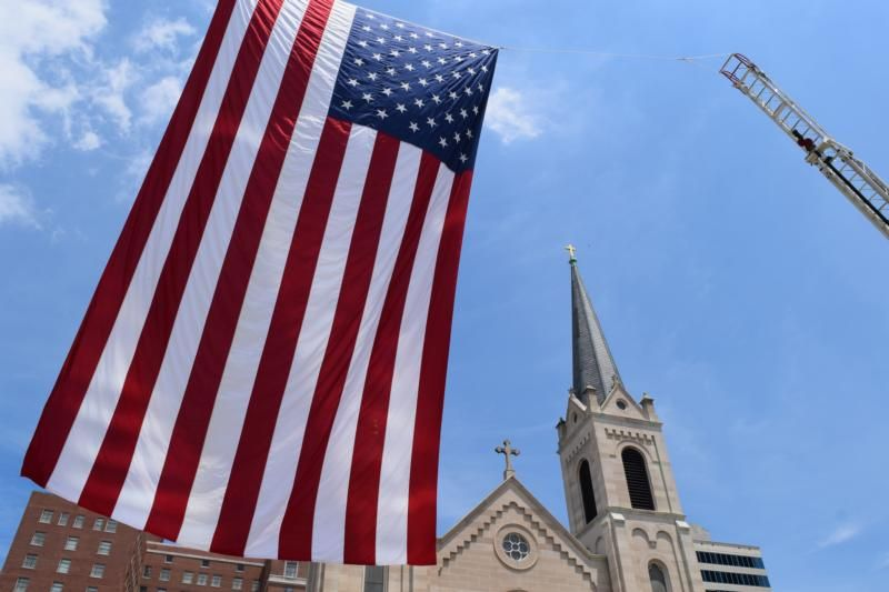A 48-foot U.S. flag is seen outside Sacred Heart Church in downtown Peoria, Ill. What is the role of the Catholic citizen in a representative democracy as it is practiced in the United States? (CNS photo/Tom Dermody, Catholic Post)
