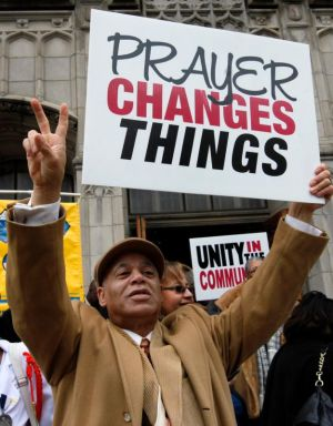 A man holds up a sign to cars outside St. Martin de Porres Church in Chicago. Well-known recent killings in the U.S. took the lives both of law enforcement officers and African-American citizens, and sparked racial unrest. The killings signaled that all is not well in society. (CNS photo/Karen Callaway, Catholic New World)