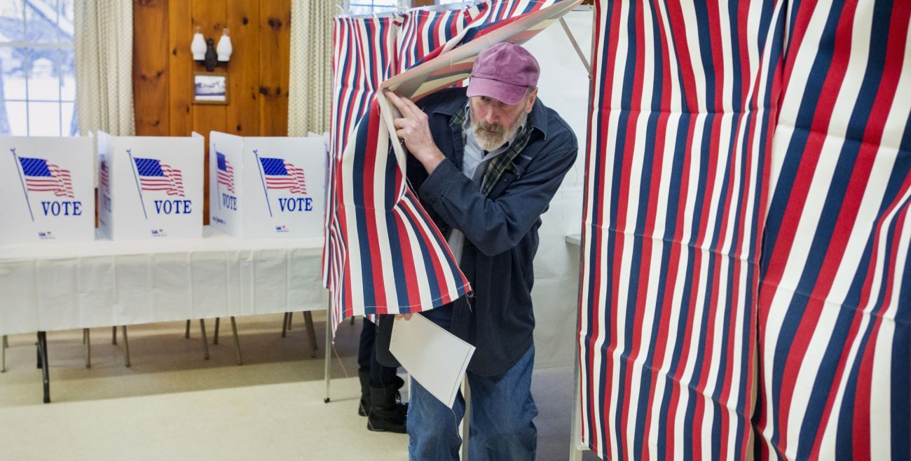 A man exits a voting booth in Laconia, N.H., Feb. 9. (CNS photo/Michael Reynolds, EPA)