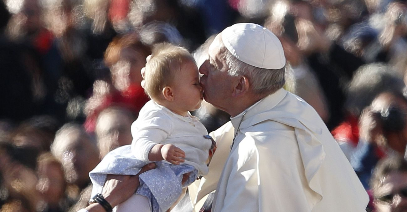Pope Francis kisses a baby during his general audience in St. Peter's Square at the Vatican Oct. 12. (CNS photo/Paul Haring)