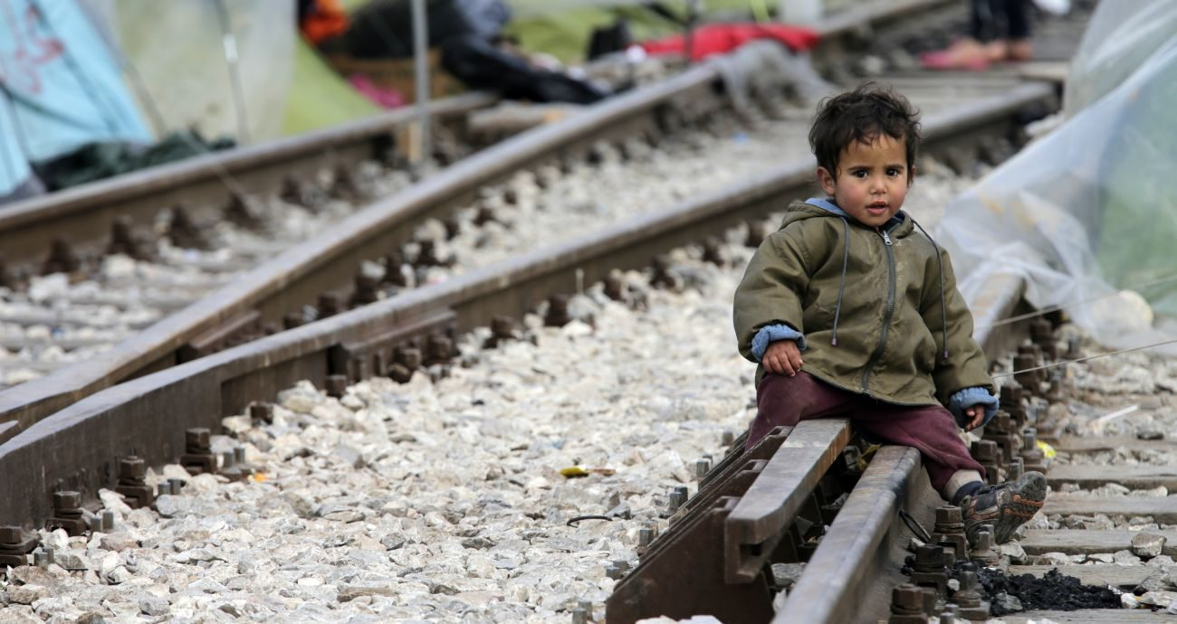 A child sits on railroad tracks near a makeshift camp for migrants in late March at the Greek-Macedonian border near the village of in Idomeni, Greece. Children are the most vulnerable and hardest hit among the world' s migrants and require special protection, Pope Francis said. (CNS photo/Armando Babani, EPA)