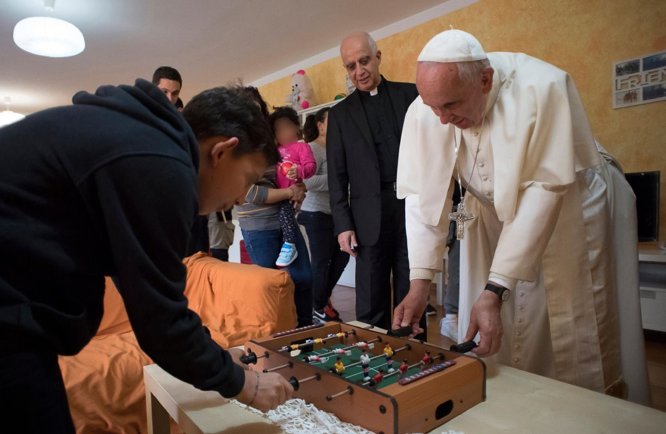 Pope Francis plays table soccer with a young resident during an Oct. 14 visit to Rome's SOS Children's Village. Young people are searching for meaning, and the best response is to go out to where they are, stop and listen to them and then call them to follow Jesus, the pope said Oct. 21. (CNS photo/L'Osservatore Romano)