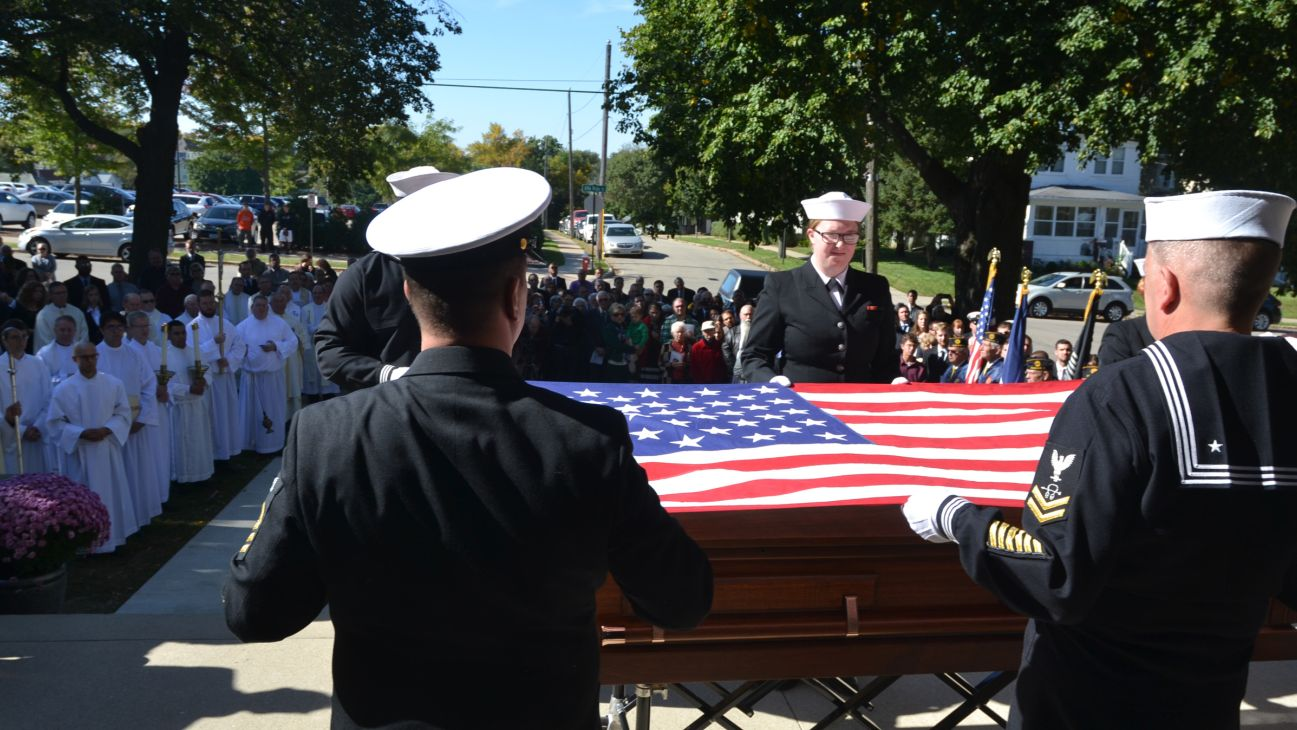 A Navy honor guard Oct. 8 folds the flag that sat atop the casket holding the remains of a World War II chaplain outside a chapel in Dubuque, Iowa. The chaplain was Father Aloysius Schmitt, an Iowa priest who perished while helping rescue survivors of the Dec. 7, 1941, attack on the USS Oklahoma at Pearl Harbor. His remains were only recently identified and returned to the Archdiocese of Dubuque. (CNS photo/Dan Russo, The Witness)