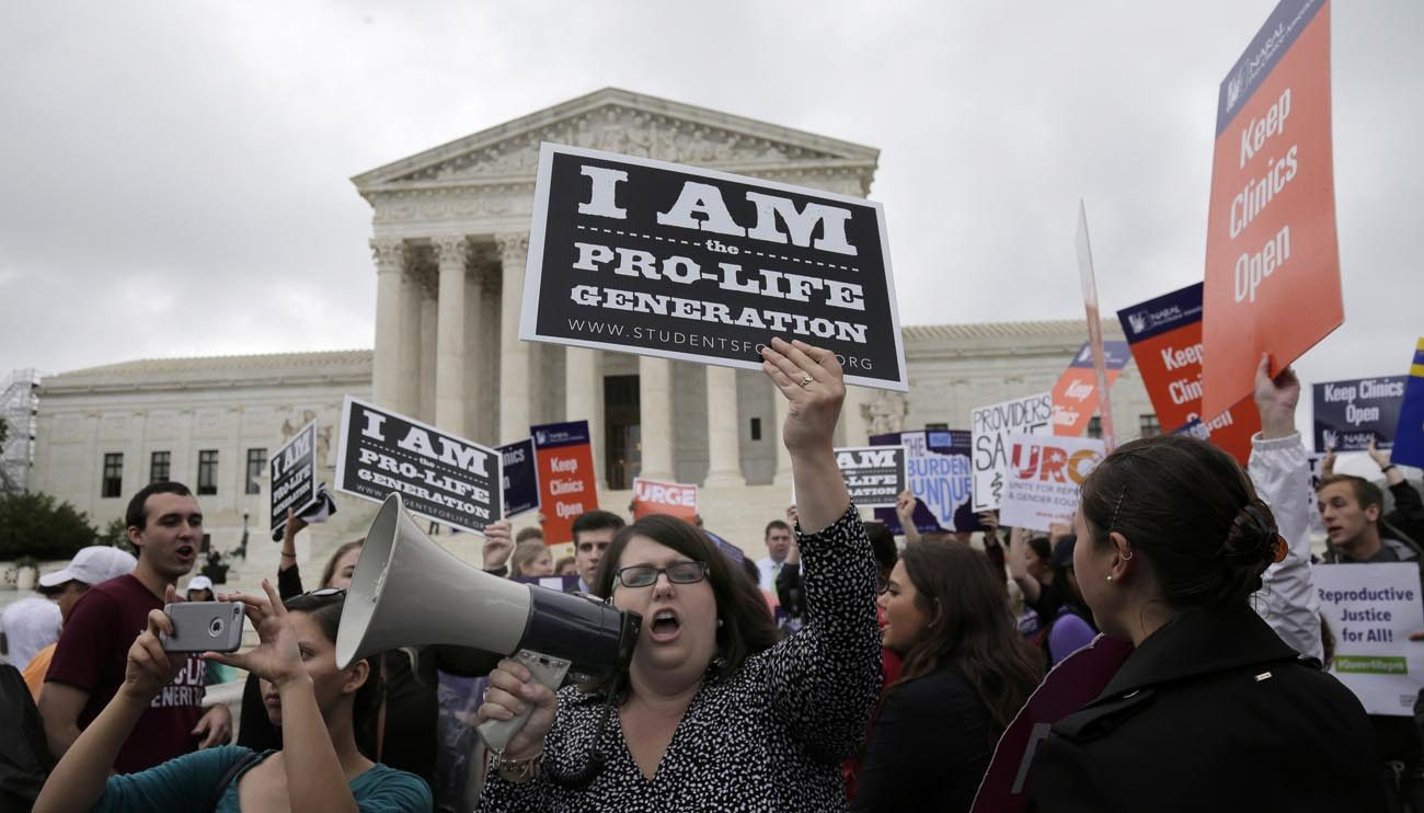 A pro-life supporter yells in a megaphone in front of the U.S. Supreme Court June 23. (CNS photo/Andrew Gombert, EPA)