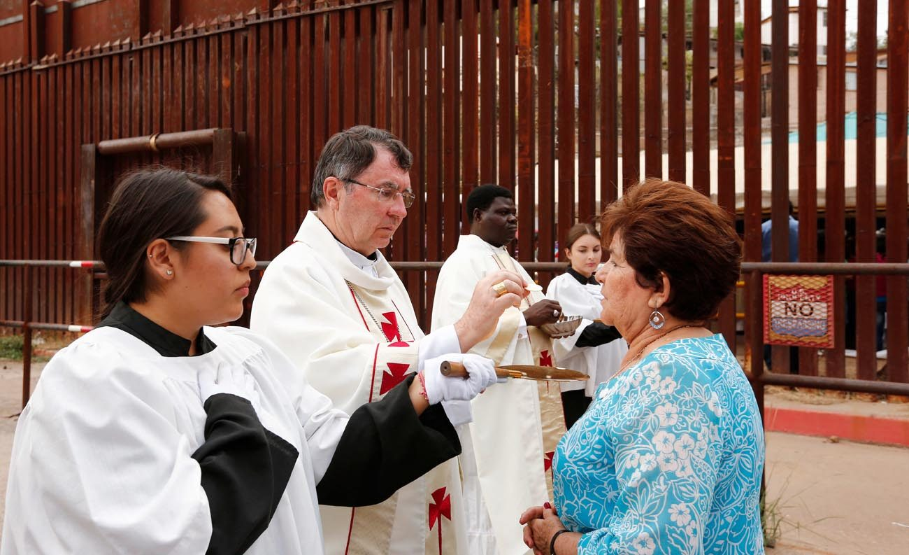 Archbishop Christophe Pierre, apostolic nuncio to the United States, gives Communion during Mass at the international border in Nogales, Ariz., Oct. 23. Dioceses Without Borders,  an effort of Mexico's Nogales Diocese and the U.S. dioceses of Phoenix and Tucson, Ariz., organized the liturgy celebrated on both sides of the U.S.-Mexico border. (CNS photo/Nancy Wiechec)
