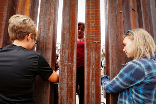 Young women reach through the international border fence to hold hands and pray the Our Father with those on the other side during Mass Oct. 23 in Nogales, Ariz.  (CNS photo/Nancy Wiechec)