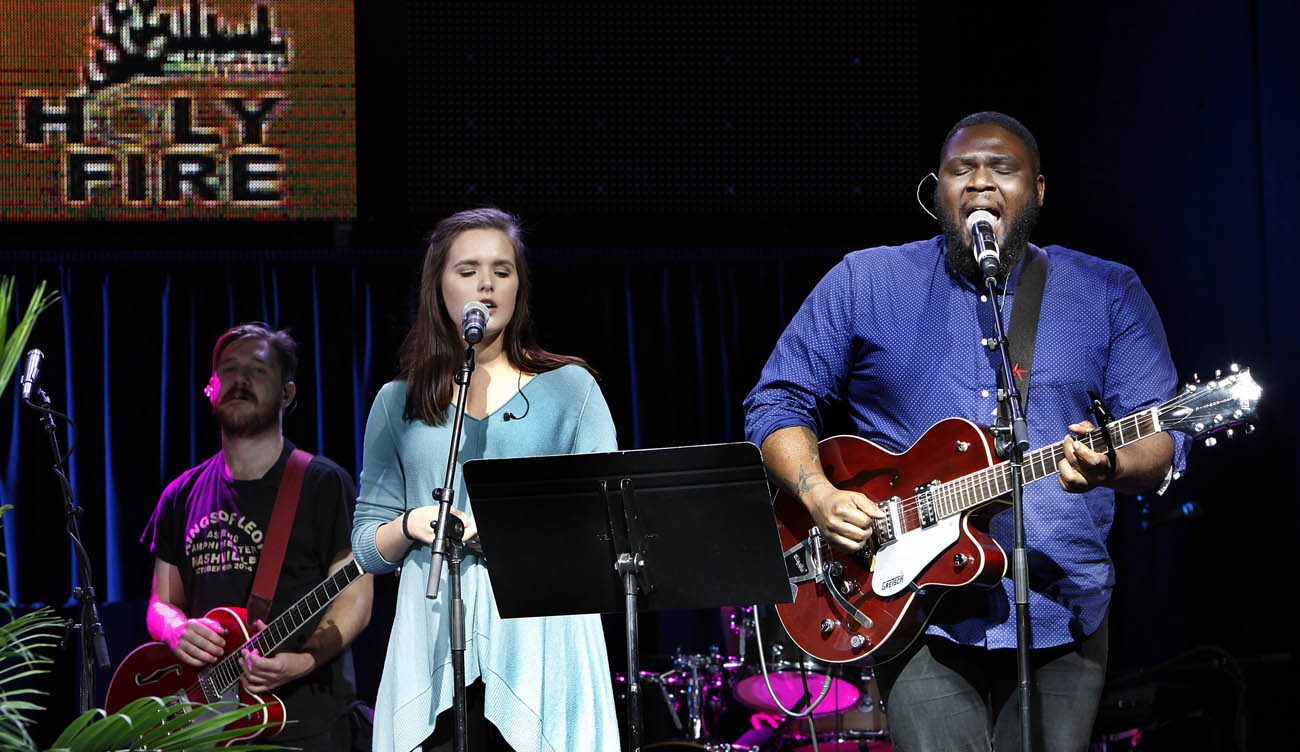 Ike Ndolo, a Catholic music minister and worship leader, right, sings during Mass attended by thousands of sixth-graders through ninth-graders Oct. 15 during the Holy Fire event in Chicago. (CNS photo/Karen Callaway, Catholic New World)