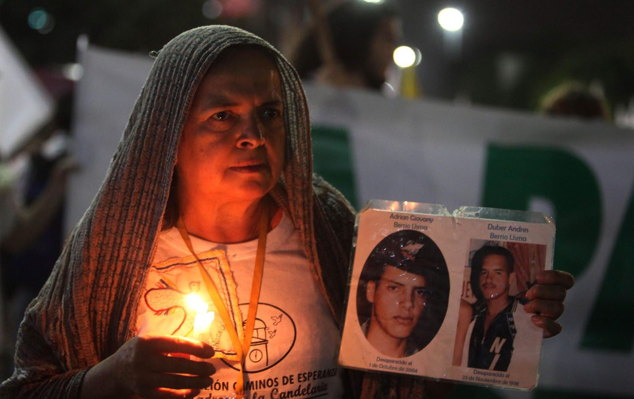 A woman holding a candle and images of disappeared victims takes part in a rally for peace Oct. 7 in Medellin, Colombia. Colombia's Catholic bishops urged the government and armed rebels to commit to an indefinite cease-fire while a new peace deal is negotiated. (CNS photo/Luis Eduardo Noriega A., EPA)