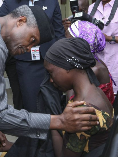 Nigerian Vice President Yemi Osinbajo consoles one of the 21 released Chibok girls Oct. 13 in Abuja. Three Catholic leaders welcomed the release of some of the girls kidnapped in 2014 from a school in Chibok and urged the Nigerian government to prioritize the release of the remaining girls. (CNS photo/EPA)