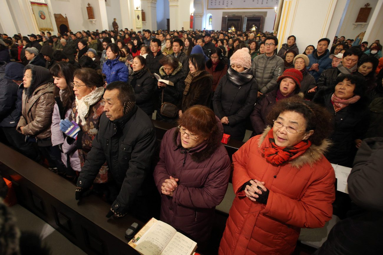 People pray during a 2013 Mass in Qingdao, China. Catholic experts have warned that new rules on religion in China could severely hamper the church's work. (CNS photo/Wu Hong, EPA)