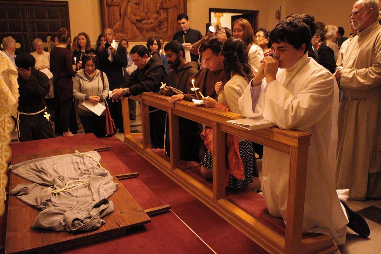 Followers of St. Francis pray over a habit as they gather Oct. 3 at the Franciscan Monastery of the Holy Land in Washington to mark the passing of St. Francis from this world into heaven. Some Franciscans say Pope Francis is helping a revival of Franciscan spirituality in modern times. (CNS photo/Rhina Guidos)
