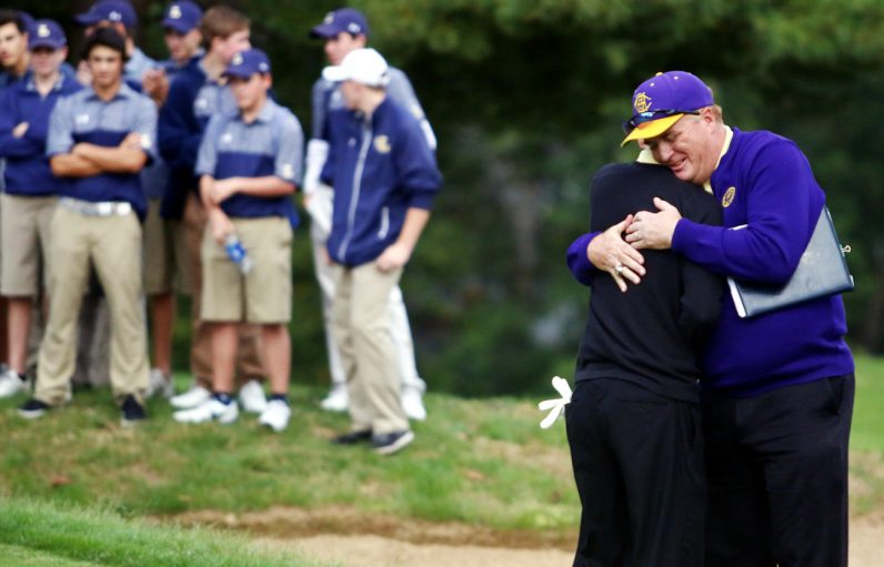 Roman Catholic coach Daniel Hoban congratulates Roman's Alex Durelli after he won the individual Catholic League  championship in a sudden death playoff.
