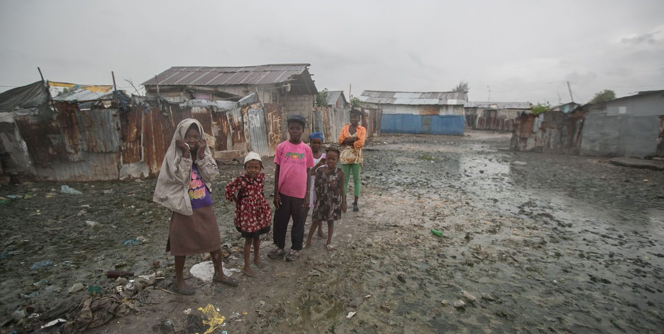 Hatian children stand in mud outside their homes Oct. 3 in Cite Soleil, a slum in Port-au-Prince, hours before Hurricane Matthew hit the island nation. Hurricane Matthew roared into the southwestern coast of Haiti Oct. 4, threatening a largely rural corner of the impoverished country with devastating storm conditions as it headed north toward Cuba and the eastern coast of Florida. (CNS photo/Bahare Khodabande, Reuters)