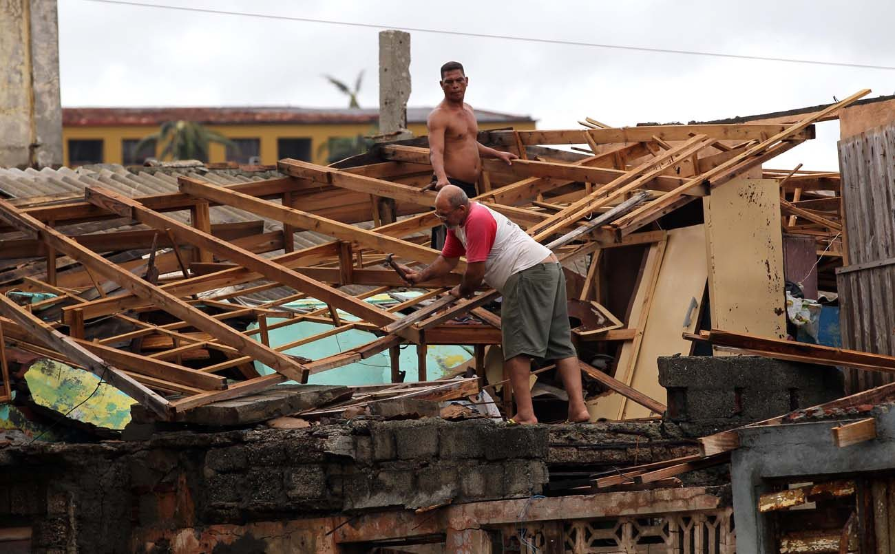 Men work on repairing the roof of a home after Hurricane Matthew swept through Baracoa, Cuba. The powerful hurricane left serious damage at the eastern end of the island, with landslides, toppling electricity poles and cutting off roads by flooding. The hurricane was expected to hit Florida's Atlantic coastal area late Oct. 6.(CNS photo/Alejandro Ernesto, EPA)