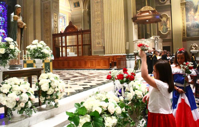 Children present flowers before the Blessed Mother after Mass.