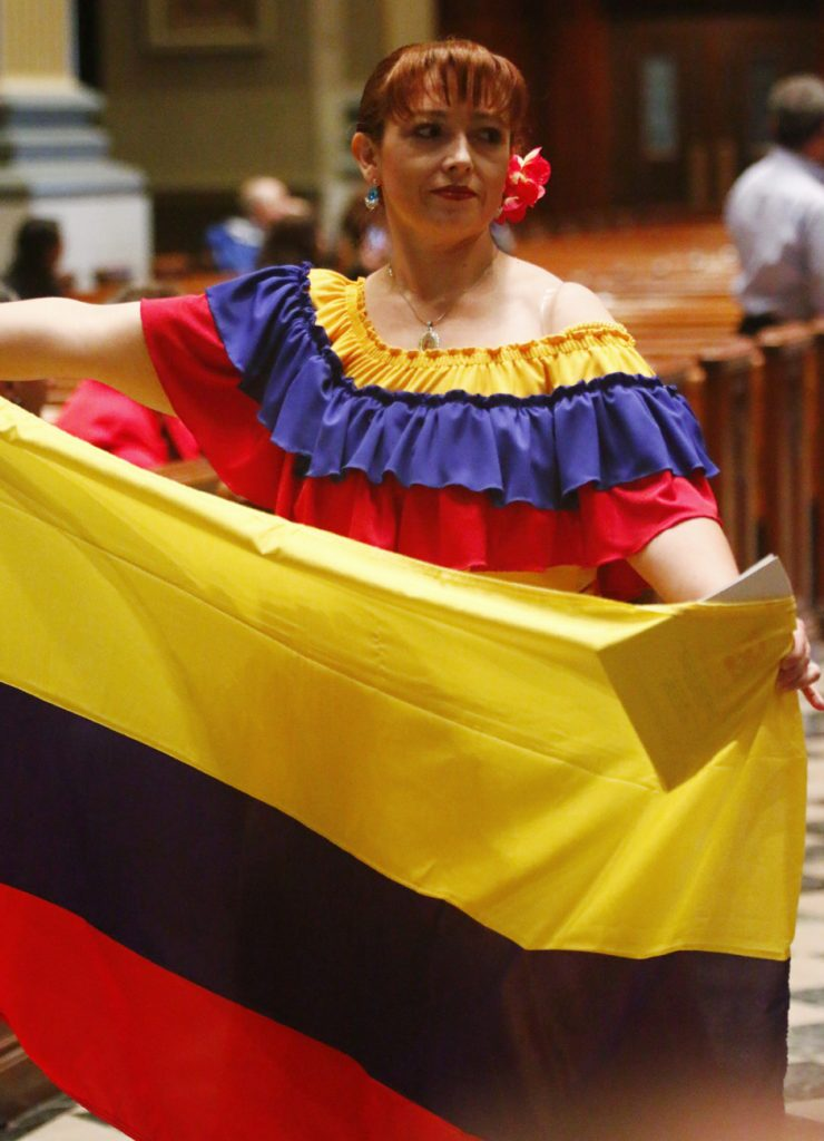 A woman proudly displays the flag of her homeland, Colombia.