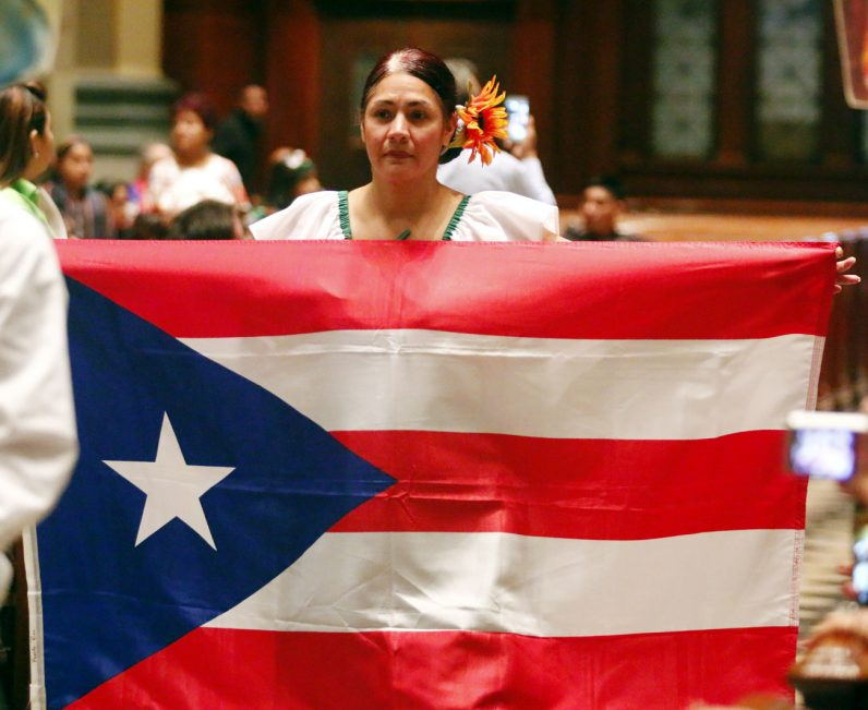 Carmen W. Mendoza, from St. Martin of Tours Parish in Philadelphia, carries the flag of Puerto Rico during the procession before Mass.