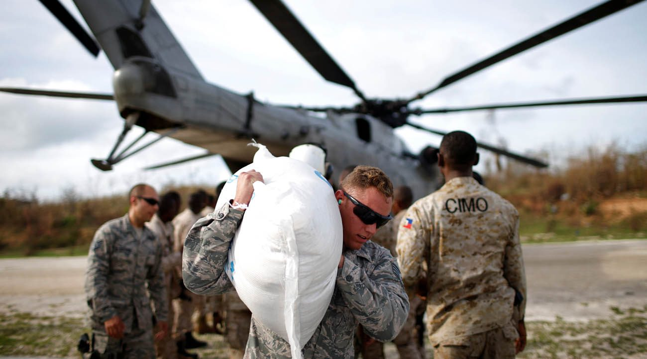 A soldier carries relief aid Oct. 9 after Hurricane Matthew swept through Jeremie, Haiti. (CNS photo/Carlos Garcia Rawlins, Reuters)