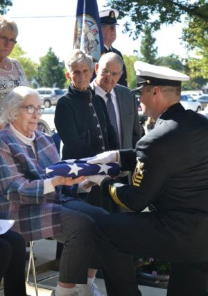 Rose Foley, the niece of Father Aloysius Schmitt, a Navy chaplain and the first U.S. chaplain killed in World War II, receives a flag during military honors after a funeral Mass for her uncle in Dubuque, Iowa, Oct. 8. The flag sat atop the casket holding Father Schmitt's remains. (CNS photo/Dan Russo, The Witness)