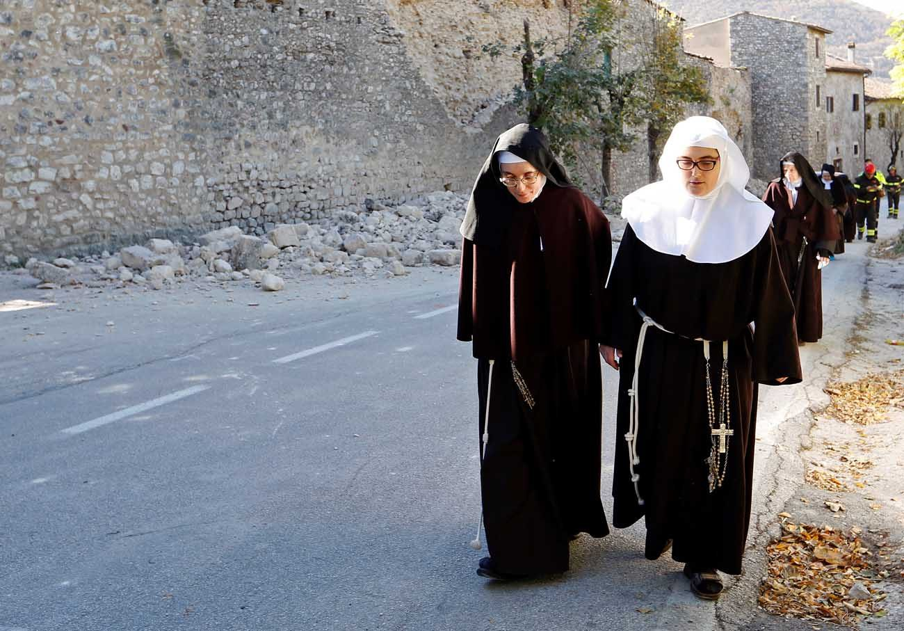 Nuns walk next to a partially collapsed wall Oct. 30 following an earthquake in Norcia, Italy. Thousands of people in central Italy have spent the night in cars, tents and temporary shelters following the fourth earthquake in the area in three months.(CNS photo/Remo Casilli, Reuters)