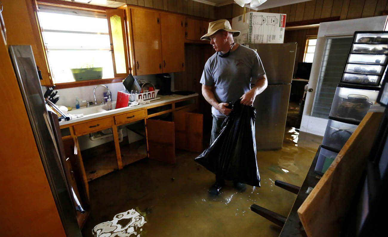 A man stands in his flooded kitchen in late August in Ascension Parish, La. A priest and deacon in the Diocese of Baton Rouge, La., have developed a Home Starter Kit program to help flood victims in Louisiana refurnish their houses. (CNS photo/Jonathan Bachman, Reuters)