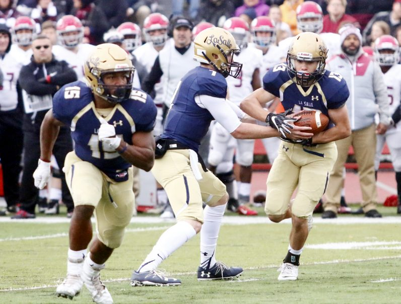 La Salle quarterback Tom Lamorte hands the ball off to running back Manny Quiles.