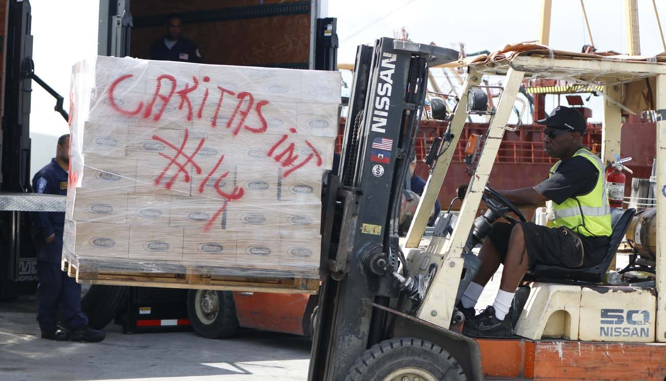 Workers move a pallet of donated items to the Betty K VI, a cargo ship moored on the Miami River Oct. 14, as the first load of emergency relief supplies organized by volunteers in the Miami Archdiocese was prepared for shipping to Miragoane, Haiti. The Haitian people are living amid the destruction caused by Hurricane Matthew in early October. (CNS photo/Ana Rodriguez-Soto, Florida Catholic)