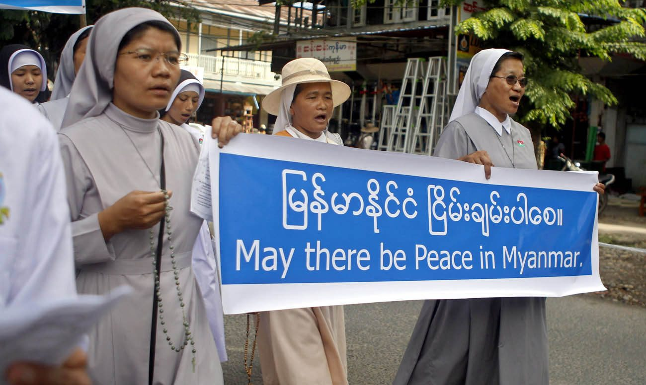 "Nuns carry a banner reading ""May there be peace in Myanmar"" during an Oct. 22 protest in Myitkyina in opposition to the country's civil war. Retired Archbishop Paul Zinghtung Grawng of Mandalay said the Kachin people are ""very fearful"" and have ""little hope of peace"" any time soon. (CNS photo/Seng Mai, EPA)"