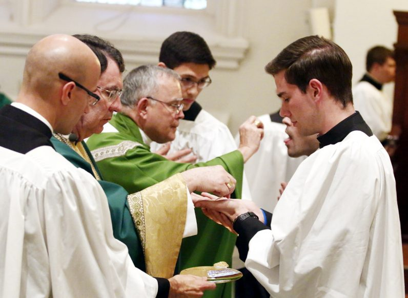 Seminarian Michael Bollinger from St. Agnes Parish in Sellersville receives Communion from Archbishop Christophe Pierre during his visit to St. Charles Borromeo Seminary.