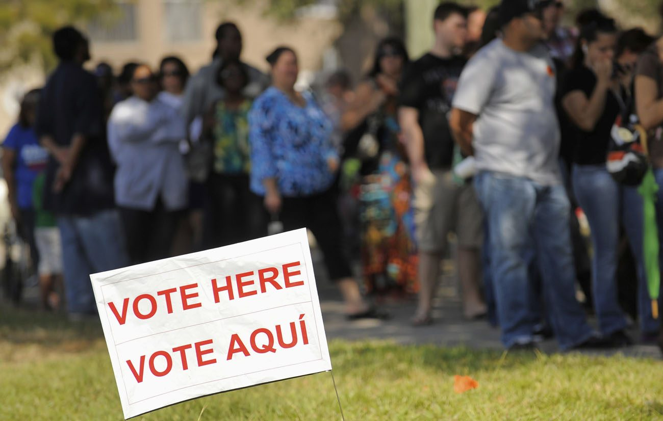 A sign in English and Spanish is seen as people wait to vote in 2012 outside a polling place in Kissimmee, Fla. A Pew Research Center poll released Oct. 10 shows Hispanic Americans give nearly a 5-1 edge to Democrats over Republicans as the party they feel is more concerned for them. (CNS photo/Scott A. Miller, Reuters)